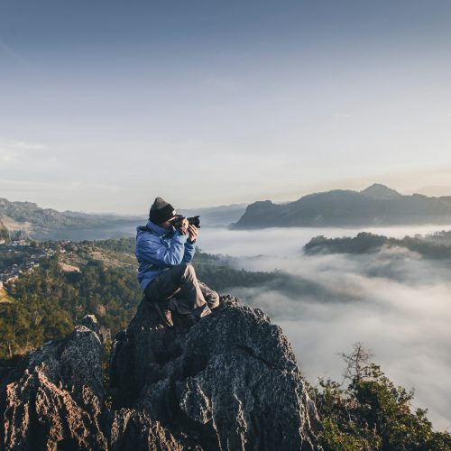 person holding camera on a mountain top